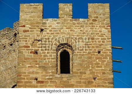 Castle Battlements With Merlons And Window Against Blue Sky