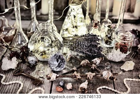 Magic Bottles With Lights, Pentagram, Crystal, Lavender Flowers And Ritual Objects On Witch Table. H