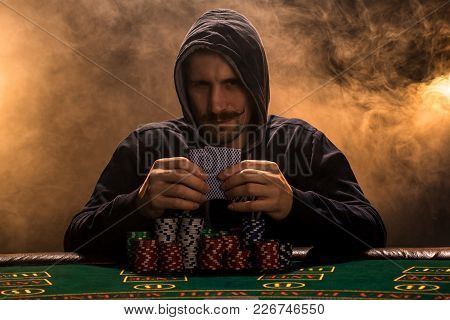 Portrait Of A Professional Poker Player Sitting At Poker Table. A Man In A Hood With Cards In His Ha