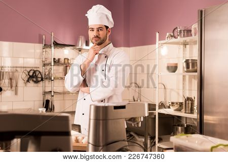 Portrait Of Pensive Confectioner Standing At Counter In Restaurant Kitchen