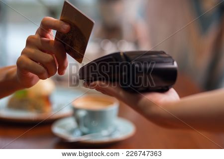 Credit Card Usage. Moment Of Payment With A Credit Card Hold By Female Hand Through Terminal Which C