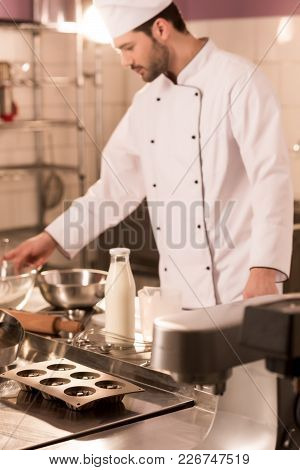 Selective Focus Of Confectioner Standing At Counter In Restaurant Kitchen