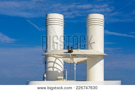 Two Security Cameras By White Smokestacks On Cruise Ship