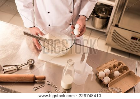 Partial View Of Confectioner With Raw Eggs In Hand Making Dough In Restaurant Kitchen