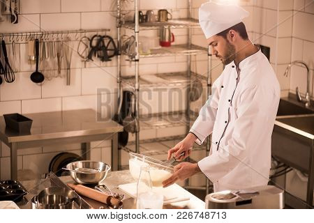 Side View Of Confectioner In Chef Hat Making Dough In Restaurant Kitchen
