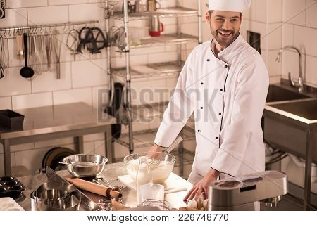 Cheerful Confectioner Standing At Counter In Restaurant Kitchen