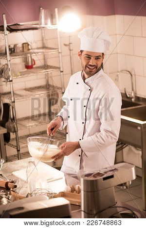 Smiling Confectioner In Chef Hat Making Dough In Restaurant Kitchen