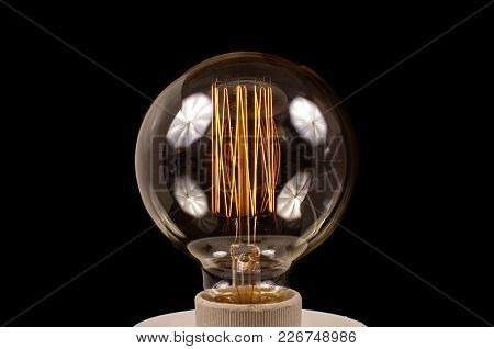 Old Style Light Bulb With Filament On Black Background