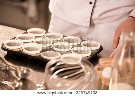 Partial View Of Confectioner At Counter With Empty Baking Forms