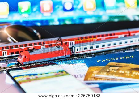 Red Toy Passenger Train, Railway Travel Tickets, Passport, Bank Card And Eyeglasses On Laptop Or Not