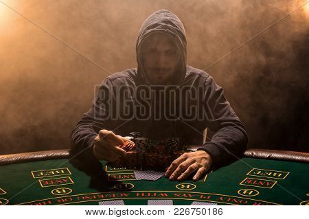 A Man In A Hoodie Sweatshirt Bets At The Poker Table, Looks Directly At The Camera. The Whole Room I