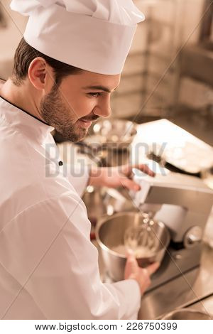 Side View Of Confectioner Cooking Dessert In Restaurant Kitchen