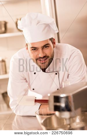 Portrait Of Smiling Confectioner In Chef Hat In Restaurant Kitchen