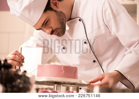 Focused Confectioner Making Sweet Cake In Restaurant Kitchen