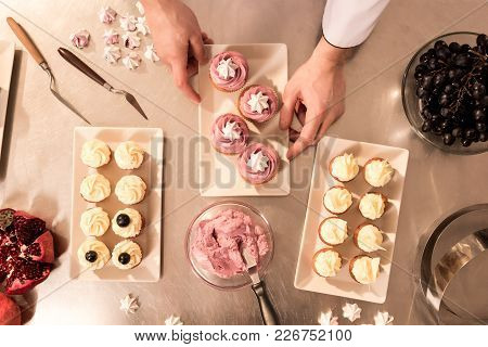 Top View Of Confectioner Arranging Cupcakes On Plate
