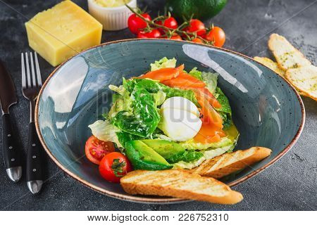 Caesar Salad With Egg, Salmon, Avocado, Cherry Tomatoes And Grilled Bread, Close Up View. Tasty Food