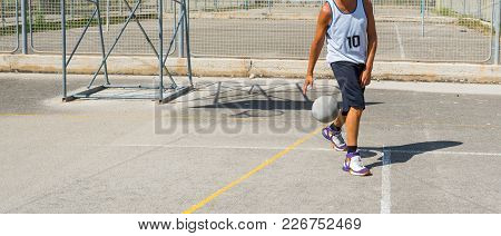 A Basketball Player Dribbling In A Playground