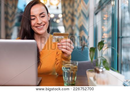 Credit Card Number. Joyful Jolly Beautiful Woman Examining Credit Card Number While Staring At It An
