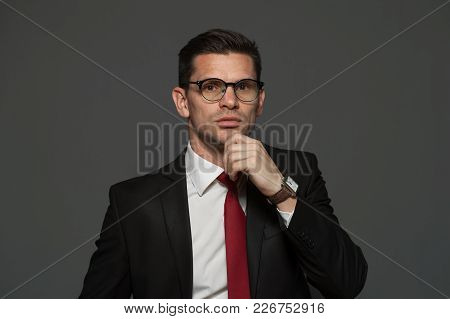 Thoughtful Businessman With Glasses And Formal Attire Ponders About Shares And Growing Exchange Rate