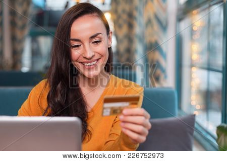 Pay Anywhere. Pretty Joyful Merry Woman Using Credit Card While Gazing Down And Grinning