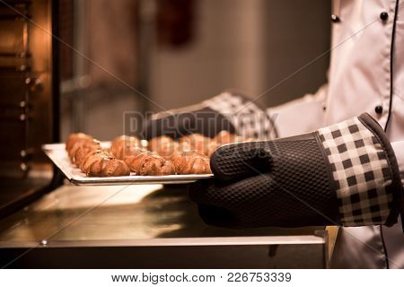 Partial View Of Confectioner Taking Eclairs On Baking Pan Out Of Oven