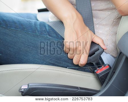 Closeup Woman Hand Sitting Inside Car Fastening Seat Belt. Safety Belt Safety First.