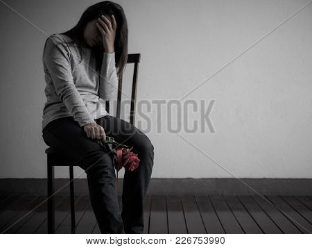 Depressed Broken Hearted Woman Sitting And Crying With Red Rose Alone In Dark Room At Home. Lonly ,