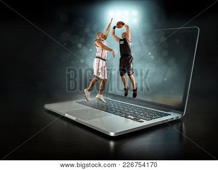 Caucassian Basketball Player in dynamic action with ball in a professional sport game play on the laptop.