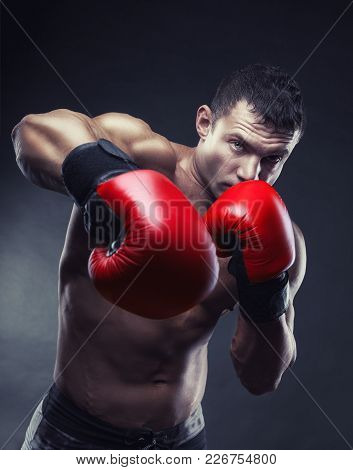 Boxing Concept. Boxer With An Aggressive Look In Red Boxing Gloves Before A Fight Against A Black Ba