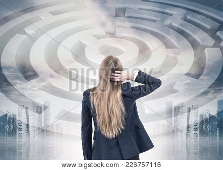Rear View Of A Confuesed Blonde Businesswoman Scratching Her Head And Looking At A Labyrinth Sketch,