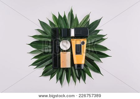 Top View Of Arranged Barber Tools On Green Leaves Isolated On Grey