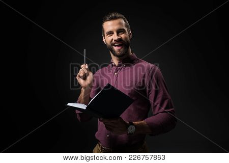 Portrait Of Excited Businessman With Notebook Isolated On Black