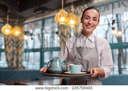 Herbal Tea. Happy Pretty Charming Waitress Holding Tray While Looking At Camera And Posing On The Bl