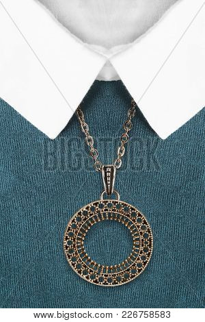 Carved Golden Pendant Hanging Over Blue Knitted Sweater With White Collar