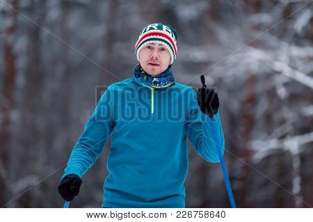 Portrait Of Male Skier On Blurred Background In Winter Forest