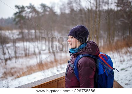 Photo Of Side View Of Woman With Backpack On Blurred Background In Forest At Winter