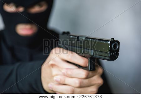 Terrorist Or Burglar In Black Mask Shooting The Gun Aiming, Robber Concept