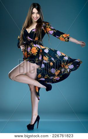 Young Fashionable Brunette Woman In Dress With Floral Print In High Heels Posing In Studio On Dark B