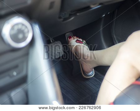 Selective Focus Of Female Foot With Red Nail Color Pushing On Pedal Of Car