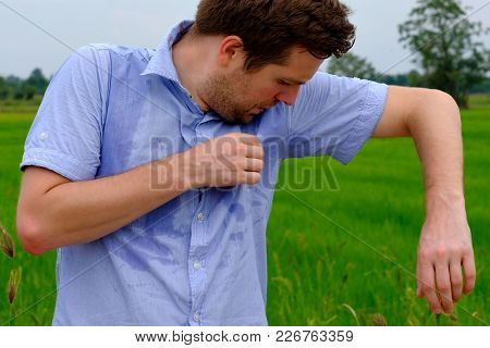 Man With Hyperhidrosis Sweating Very Badly Under Armpit In Blue Shirt Because Of Hot Weather. Travel