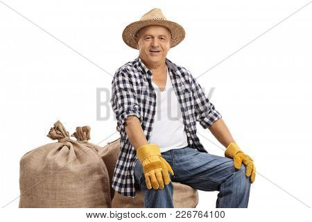 Old farmer seated on burlap sacks isolated on white background