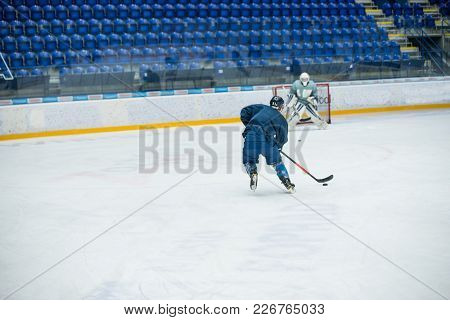Hockey Players And Goalie On The Ice In Training