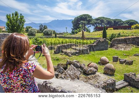 Girl Photographs The Ruins Of The Old City Of Pompeii With The Remains Of Houses And Kitchen Utensil
