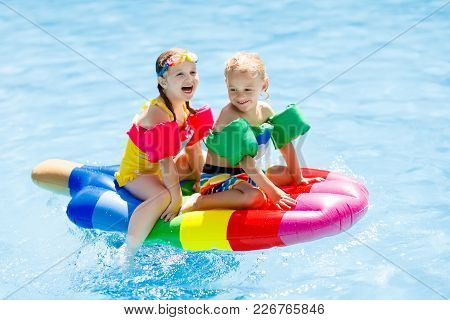 Child With Goggles In Swimming Pool. Little Girl Learning To Swim In Outdoor Pool Of Tropical Resort