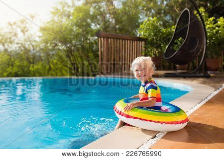 Baby with inflatable armbands in swimming pool. Little boy learning to swim in outdoor pool of tropical resort. Swimming with kids. Healthy sport activity for children. Sun protection. Swim aids. poster