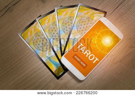 Tarot cards and smartphone with modern fortunetelling application on screen as a concept of psychic advisor or newest ways of divination