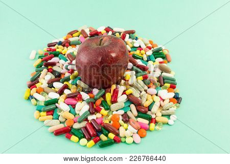 Red Delicious Apple On A Pile Of Pills Or Tablets