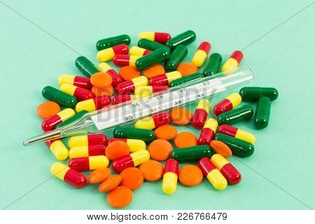Classic Thermometer On A Pile Of Pills Or Tablets