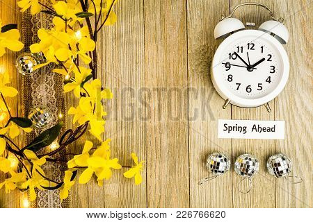 Daylight Savings Time Spring Ahead Concept Top Down View With White Clock And Yellow Forsythia Flowe