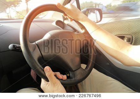 Left Hand Below Right Hand And Hold The Steering Wheel Of The Car.